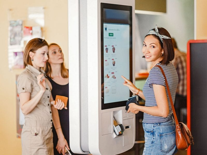 Diners using a foodservice kiosk to order a meal.