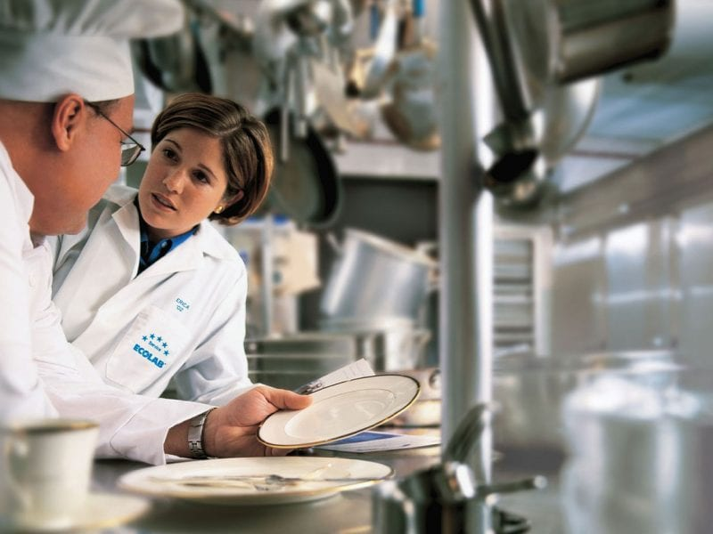Two chefs inspect clean dishes in a restaurant kitchen.