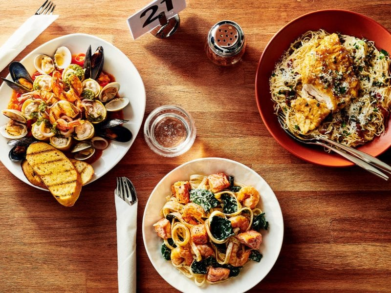 Pasta dishes with seafood on top.